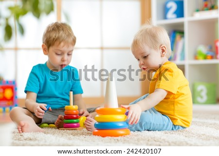 children brothers playing together in nursery at home - stock photo
