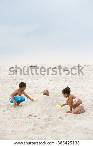Children burying father in sand - stock photo