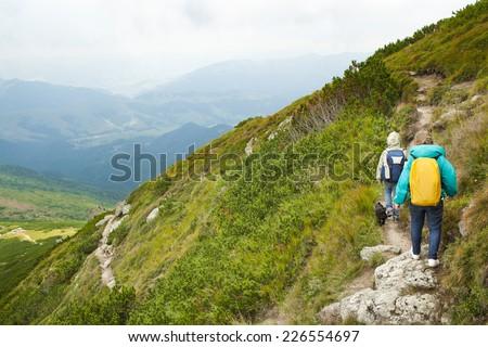 Children climbing green mountain in idyllic landscape - stock photo