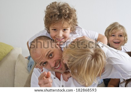 Children climbing over their father on the sofa - stock photo