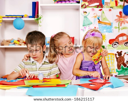 Children cutting out scissors paper in preschool. - stock photo
