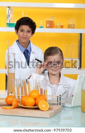 Children doing chemistry experiments with orange juice - stock photo