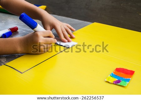 Children drawing on a yellow background. - stock photo
