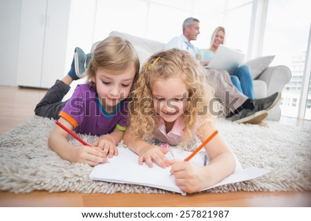Children drawing on papers while parents sitting on sofa at home - stock photo