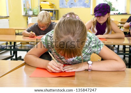 Children during a lesson in a school. In front you see a girl, she is writing on a paper. Studio light. - stock photo