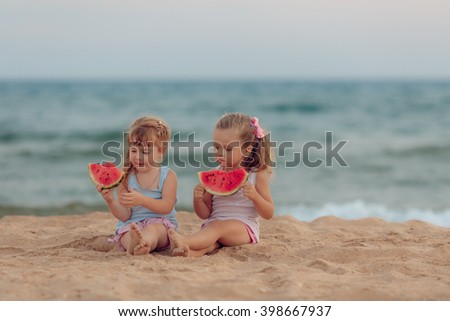 children eat ripe watermelon on the beach - stock photo