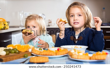 Children eating baked pastry dessert with cream and fruit in the kitchen. - stock photo