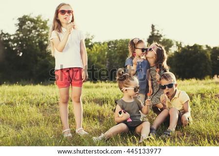 Children eating lollipops during summertime fun - stock photo