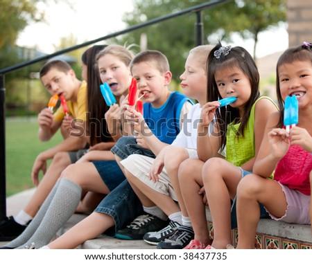 Children eating popsicles - stock photo
