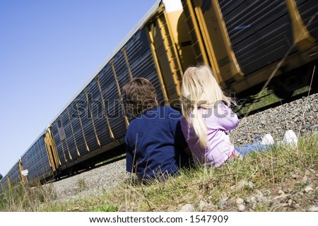 Children enjoy a passing train on a warm sunny afternoon. - stock photo