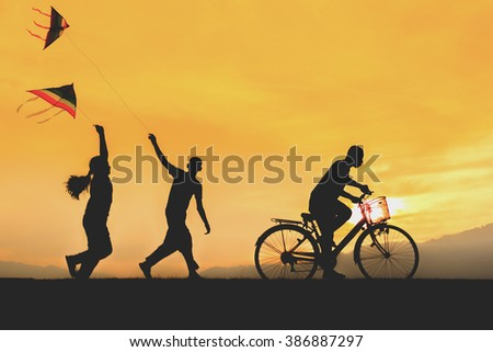 children enjoy flying a kite with ride bicycle during sunset. - stock photo