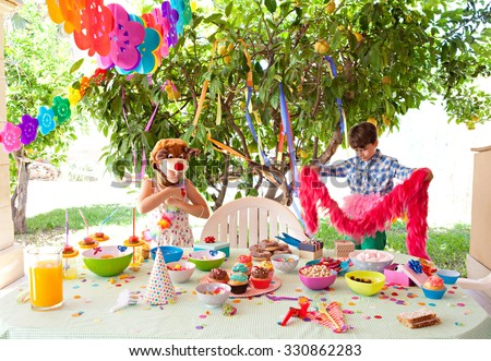 Children enjoying a bright and colorful birthday party in a home garden on a sunny day outdoors. Boy and girl eating sweets and dressing up in party with decorations, house exterior. - stock photo