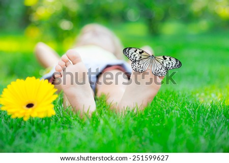 Children feet in green grass. Butterfly and spring flower. Healthy lifestyle concept - stock photo