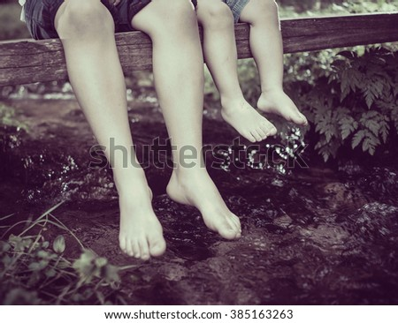 Children feet playing and having fun time on the beautiful mountain creek - stock photo