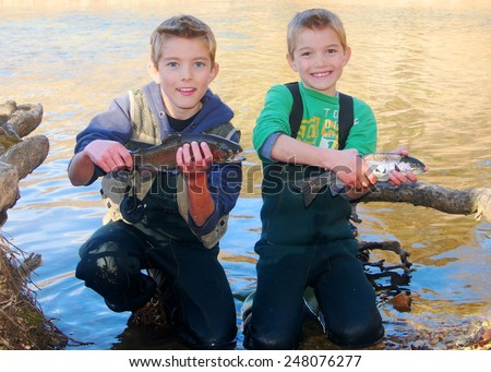 Children fishing - brothers and friends holding prize fish they caught fly fishing in a clear stream (Rainbow Trout) - stock photo