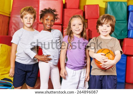 Children forming team for ball game in gym of a kindergarten - stock photo