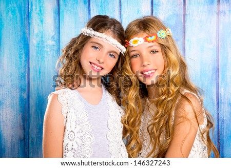 Children friends beautiful girls hippie retro style smiling together on blue wood - stock photo