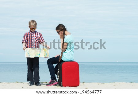 Children going for sea vacation with a luggage and a map - stock photo