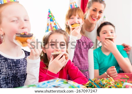 Children grabbing muffins at birthday party and cake, the kids are wearing hats, balloons and paper streamers for decoration  - stock photo