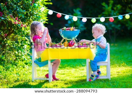 Children grilling meat. Family camping and enjoying BBQ. Brother and sister at barbecue preparing steaks and sausages. Kids eating grill and healthy vegetable meal outdoors. Garden party for child. - stock photo