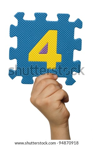 Children hand holding the number Four. White isolated multicolor number Four - stock photo