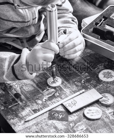 Children hands drawing a bicycle with a solid-point burner on a round plate piece made of wood (on black and white) - stock photo