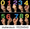 Children hands holding numbers. Black isolated multicolor numbers. - stock photo