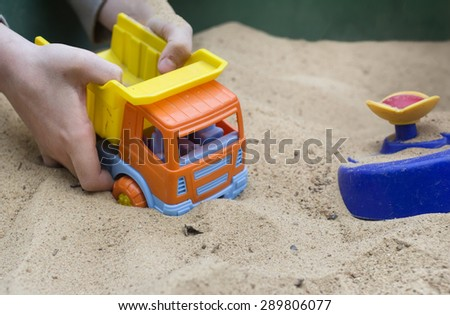 Children hands playing with a toy truck in the sandbox, outdoor shot with selective focus - stock photo