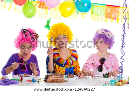 Children happy birthday party eating chocolate cake with clown wigs - stock photo