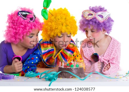 Children happy birthday party with clown wigs blowing chocolate cake candles - stock photo