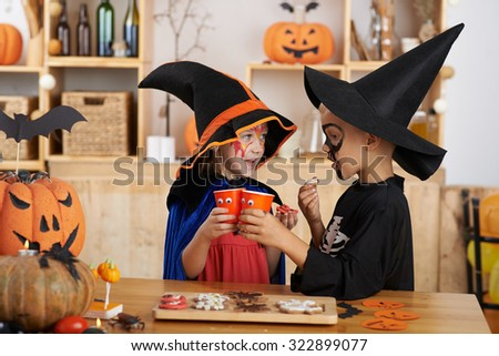 Children having drinks and eating cookies at Halloween party - stock photo