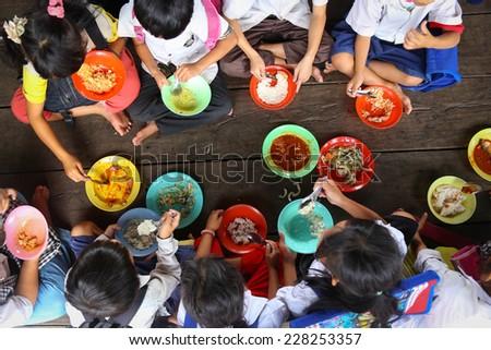Children having lunch in asian school sitting on the floor - stock photo