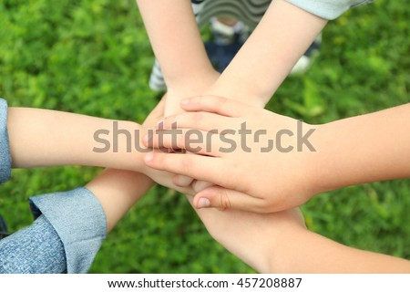 Children holding hands together on grass background - stock photo