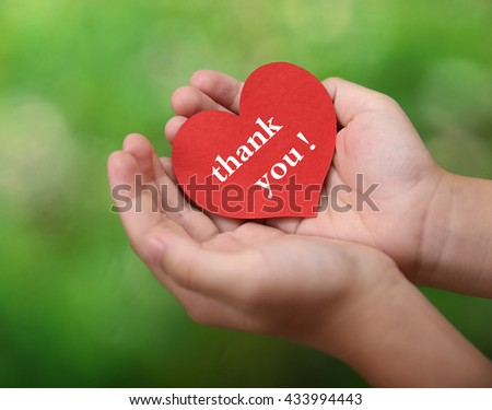 Children holding or showing card with thank you text - stock photo