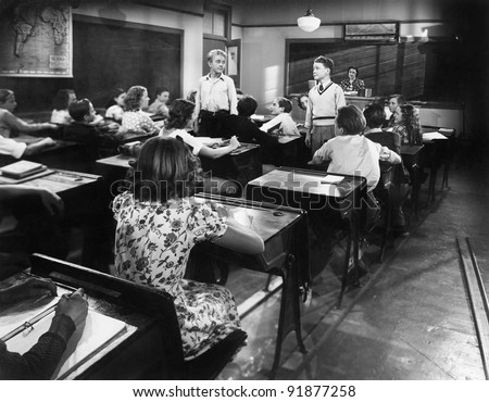 Children in a class room with a teacher and two boys looking at each other - stock photo