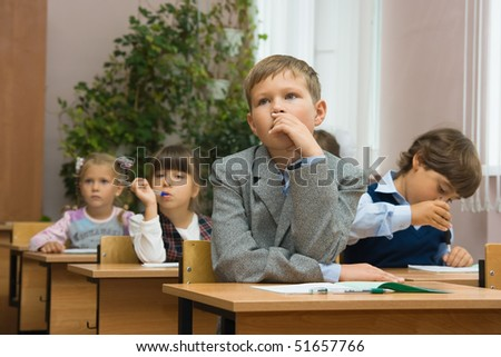 Children in a classroom at a lesson. - stock photo