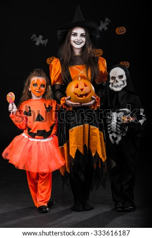 Children in costumes celebrating Halloween bats on the background - stock photo