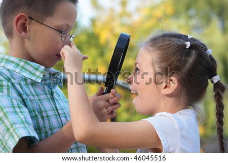 children in early fall park. little boy is looking at joyful little girl through magnifier - stock photo