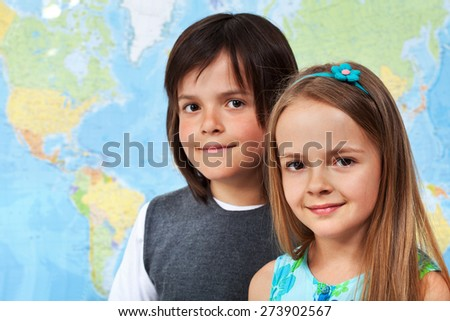 Children in geography class - portrait in front of large wall map, with copy space - stock photo