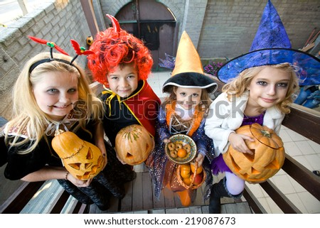children in halloween costumes with pumpkin walk in guests - stock photo