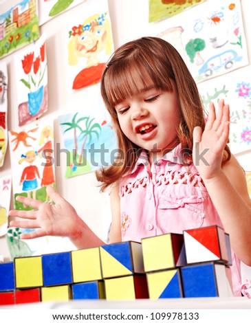 Children in kindergarten stacking block. - stock photo