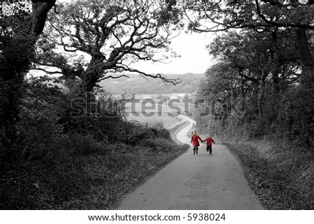 Children in red coats running up farm road - stock photo