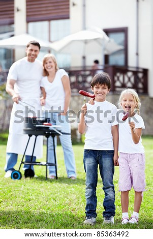 Children in the foreground with sausage in hands - stock photo