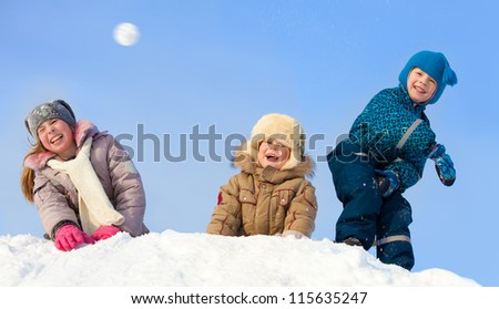 Children in winter. Happy kids playing snowball - stock photo