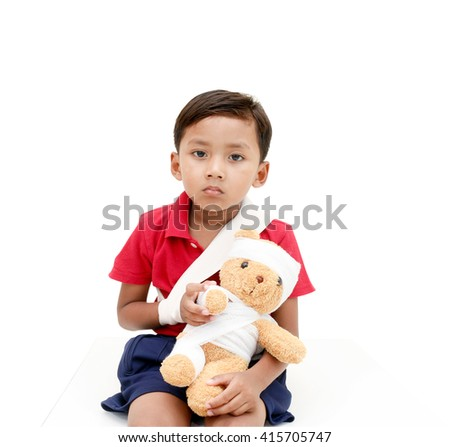 Children injured has a grimace and showing his broken arm and bandaged at head.with clipping path. - stock photo