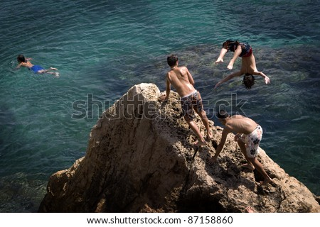Children jumping into the sea from a rock in Ibiza - stock photo