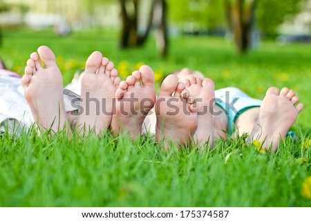 Children laying on grass. Family picnic in spring park  - stock photo