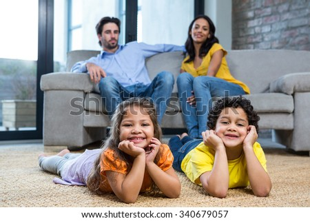 Children laying on the carpet in living room while parents on the sofa - stock photo