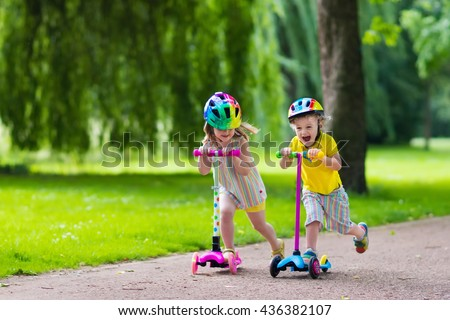 Children learn to ride scooter in a park on sunny summer day. Preschooler boy and girl in safety helmet riding a roller. Kids play outdoors with scooters. Active leisure and outdoor sport for child. - stock photo