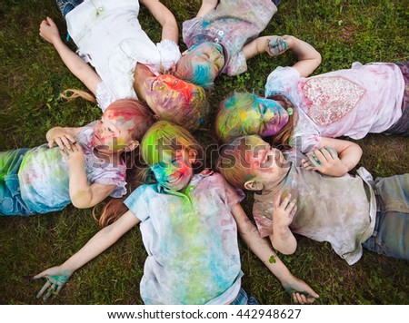 Children lie on the grass. Children painted in the colors of Holi festival lie on the grass. - stock photo